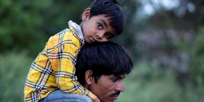 A migrant worker carries his 5-year-old son on his shoulders, New Delhi, March 26, 2020.