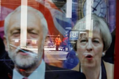 Workers in protective equipment are reflected in the window of a betting shop with a display inviting customers to place bets on tbe result of the general election with images of Britain's Prime Minister Theresa May and opposition Labour Party leader Jeremy Corbyn, in London, June 7, 2017. REUTERS/Marko Djurica