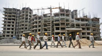 File picture shows workers walking in front of the construction site of a commercial complex on the outskirts of Ahmedabad. Photo: Reuters