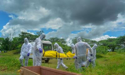 Municipality workers and family members wearing protective suits carry the body of a person who died of COVID-19 for the burial at a graveyard, in Karad, Friday, July 31, 2020. Photo: PTI