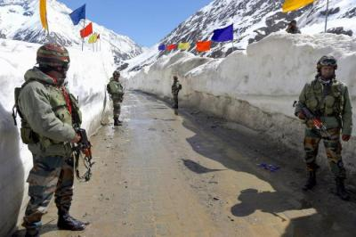 Army soldiers stand guard at snow-bound Zojila Pass, situated at a height of 11,516 feet, on its way to frontier region in Ladakh. Photo: PTI