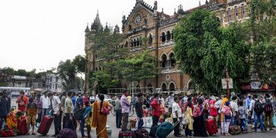 Migrant workers queue outside the Chhatrapati Shivaji Terminus to return to their hometowns in Mumbai, June 14, 2020. Photo: PTI