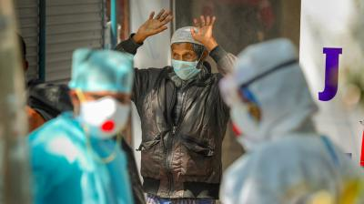 A Rohingya Muslim man prepares to walk through a full-body sanitization tunnel installed at COVID-19 dedicated Government Medical College hospital, in Jammu, Sunday, April 19, 2020. Photo: PTI