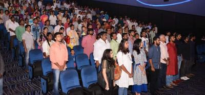 People stand in a movie theatre as the national anthem plays. Photo: PTI