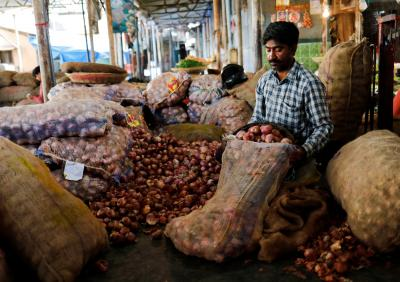 A vendor puts onions in a sack after sorting them at a vegetable market in Mumbai, India, June 12, 2018. Photo: Reuters/Danish Siddiqui