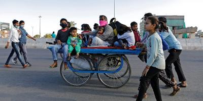 A migrant worker rides a cart with his family on a highway as they return to their villages, during a 21-day nationwide lockdown to limit the spreading of coronavirus disease (COVID-19), in Ghaziabad, on the outskirts of New Delhi, March 27, 2020. Photo: Reuters/Adnan Abidi