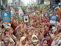 Carrying photos, families of deceased farmers protest